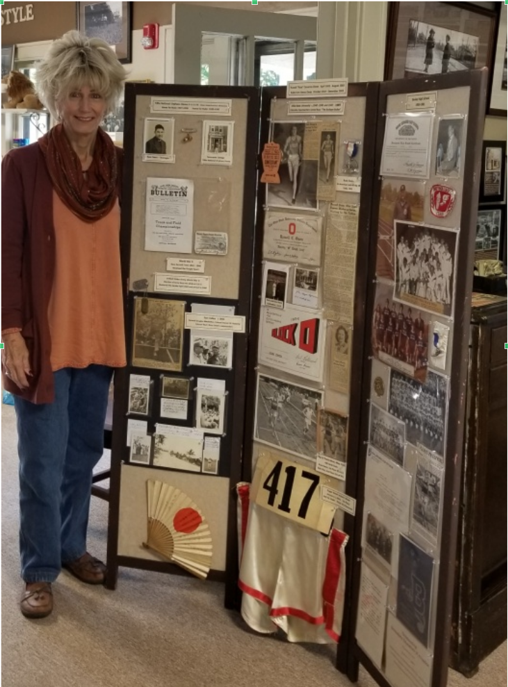 Nancy Owen-Hawkins standing by a portion of the materials she provided of her father, Russ, and her mother, Ruby.
